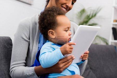 Photo pour Mère afro-américaine et petit fils avec tablette numérique à la maison - image libre de droit