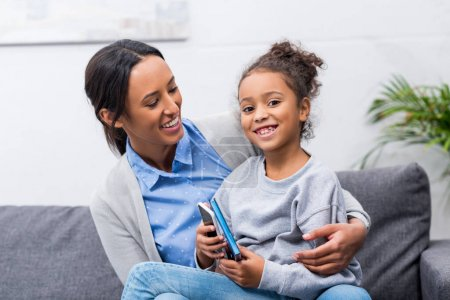 mother and daughter with smartphone
