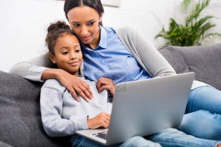 Photo pour Afro-américaine mère et fille en utilisant un ordinateur portable à la maison - image libre de droit