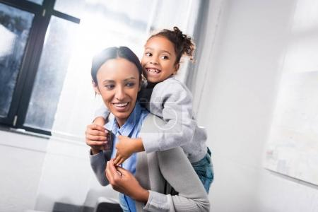 mother piggybacking her daughter