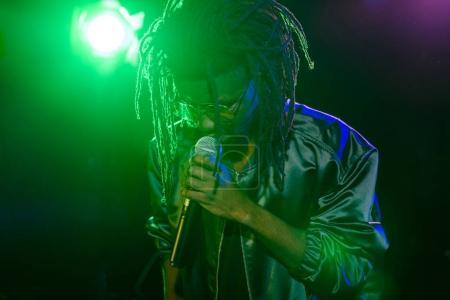 Photo pour Dj professionnel d'afro-américain avec microphone en boîte de nuit avec rétro-éclairage - image libre de droit