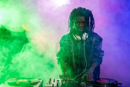 Photo for Professional african american DJ in headphones with sound mixer in nightclub - Royalty Free Image