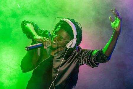 Photo pour Club africain-américain professionnel Dj casque d'écoute avec microphone sur le concert de musique de chant - image libre de droit