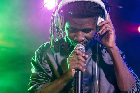 DJ in headphones with microphone on concert