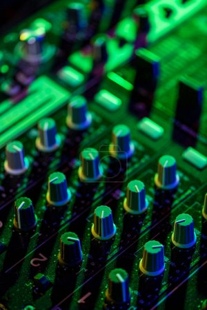 Photo for Selective focus of sound mixer in nightclub with green light - Royalty Free Image