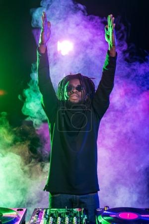 Photo for Professional african american club DJ with sound mixer in nightclub - Royalty Free Image