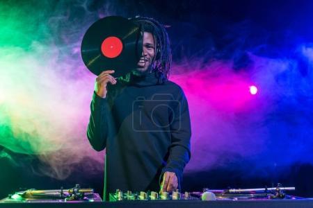 Photo pour Dj professionnel d'afro-américain avec ingénieur du son et de vinyle dans la boîte de nuit avec rétro-éclairé - image libre de droit