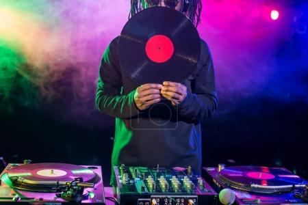 Photo for Professional african american club DJ with vinyl and sound mixer in nightclub - Royalty Free Image
