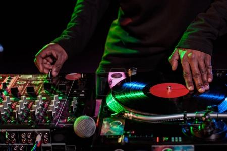 Photo for Cropped view of DJ hands with sound mixer and vinyl - Royalty Free Image