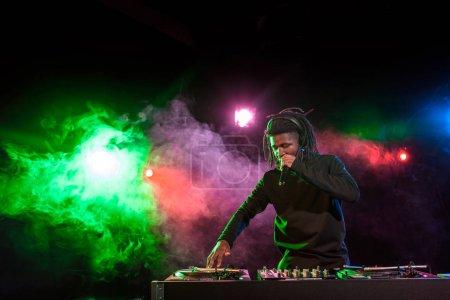 Photo pour DJ afro-américain professionnel en casque avec mixeur sonore en boîte de nuit - image libre de droit
