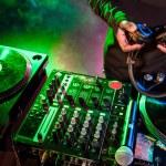 DJ with headphones over sound mixer