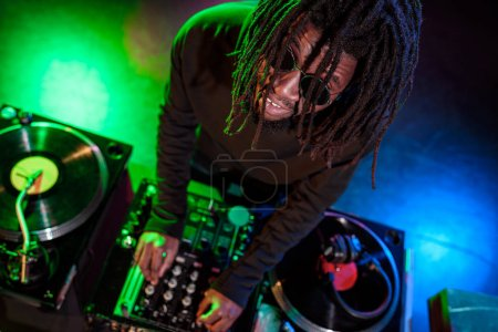 Photo for Professional african american DJ with sound mixer in nightclub - Royalty Free Image
