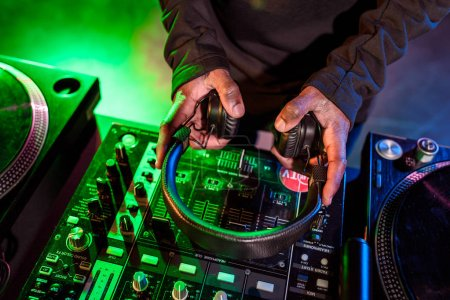 Photo pour Recadrée vue des mains de Dj maintenant casque au dessus de la table de mixage sonore - image libre de droit