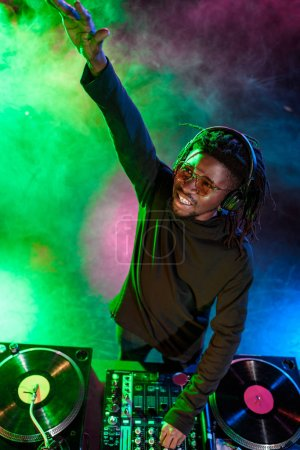 Photo for Professional african american club DJ in headphones with sound mixer on concert - Royalty Free Image