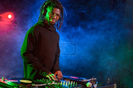 Photo pour Professionnel Dj afro-américains dans les écouteurs avec ingénieur du son en boîte de nuit - image libre de droit