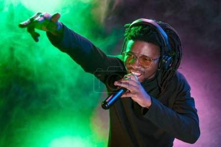 Photo for Professional african american club DJ in headphones with microphone in on concert - Royalty Free Image
