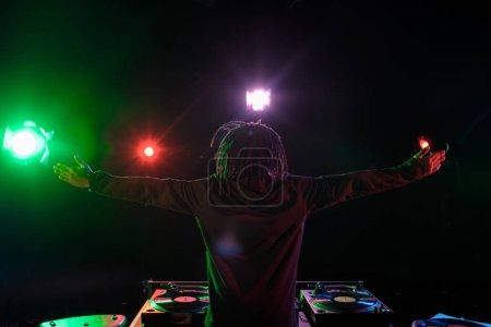 Photo pour Dj professionnel d'afro-américain avec ingénieur du son en boîte de nuit avec rétro-éclairage - image libre de droit
