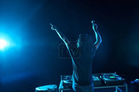 Photo for Professional african american club DJ with sound mixer on concert in nightclub - Royalty Free Image