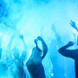 People dancing in nightclub with blue back light...