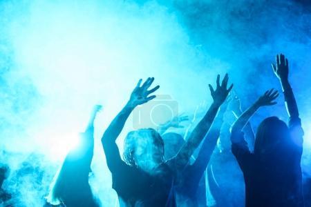 Photo pour Gens qui dansent sur la partie en boîte de nuit avec rétro-éclairage bleu - image libre de droit