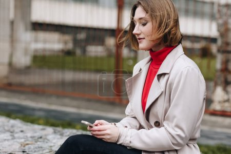 Photo for Young stylish woman using smartphone outdoors - Royalty Free Image