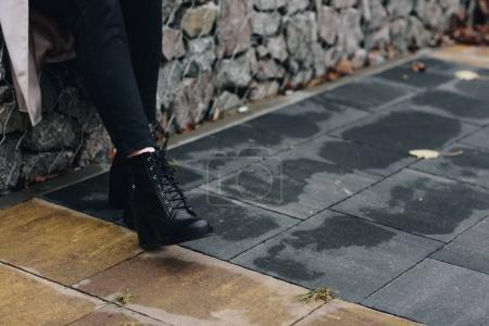 Photo pour Photo recadrée de femme en cuir élégant bottes debout à l'extérieur - image libre de droit