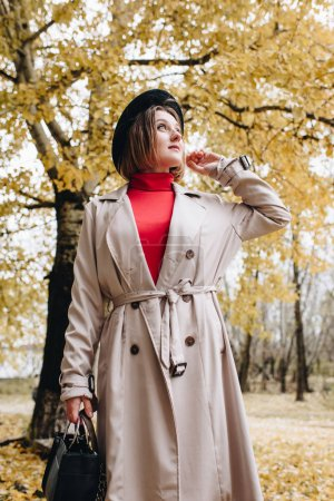 woman in trench coat at autumn park