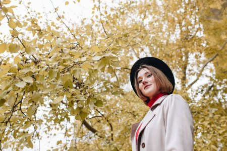 Photo pour Vue du dessous de la jeune femme élégante en trench-coat et chapeau en parc - image libre de droit