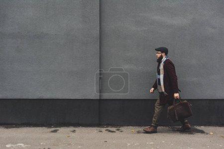 Photo pour Vue latérale de l'homme barbu dans des vêtements élégants marchant sur la rue - image libre de droit
