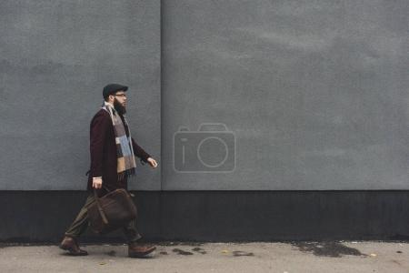 Photo for Side view of bearded man in stylish clothing walking on street - Royalty Free Image