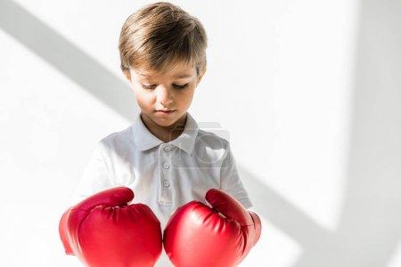 Photo pour Mignon petit garçon en regardant vers le bas sur le blanc des gants de boxe - image libre de droit