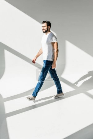 Photo for Full length view of handsome bearded man smiling and walking in studio - Royalty Free Image