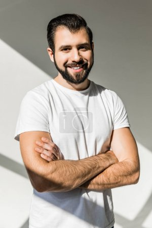 Photo for Handsome bearded young man standing with crossed arms and smiling at camera in studio - Royalty Free Image