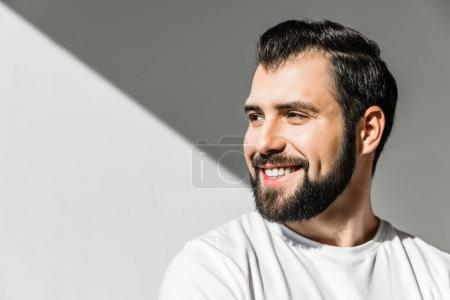 Photo for Portrait of handsome young bearded man smiling and looking away on grey - Royalty Free Image