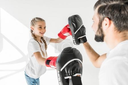Photo pour Vue latérale de l'heureux père et fille boxe ensemble sur blanc - image libre de droit