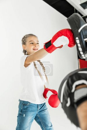 Photo for Cropped shot of father training cute little daughter in boxing gloves isolated on white - Royalty Free Image