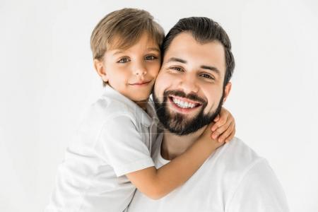 Photo pour Heureux père et fils étreignant et souriant à la caméra isolé sur blanc - image libre de droit