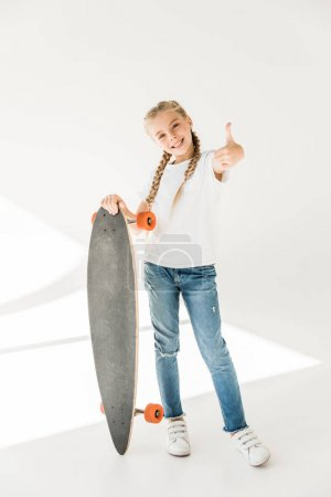 Photo for Cute happy child holding skateboard and showing thumb up on white - Royalty Free Image