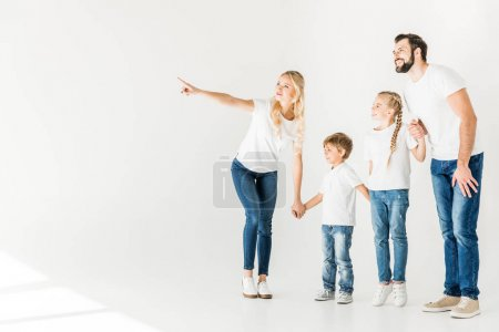 Photo for Happy young family in white t-shirts holding hands and looking away isolated on white - Royalty Free Image