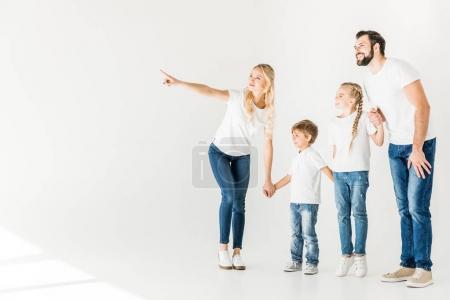 Photo pour Heureuse jeune famille en t-shirts blancs tenant la main et regardant loin isolé sur blanc - image libre de droit