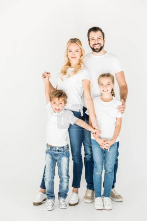 Photo for Happy young family in white t-shirts standing together and smiling at camera isolated on white - Royalty Free Image
