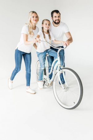 Photo for Happy parents teaching daughter riding bicycle isolated on white - Royalty Free Image