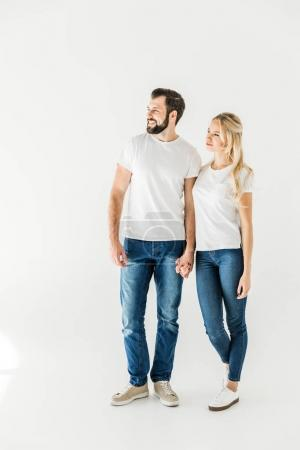 Photo for Beautiful happy young couple standing together and looking away isolated on white - Royalty Free Image