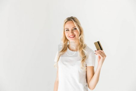 Photo for Beautiful young woman holding credit card and smiling at camera - Royalty Free Image