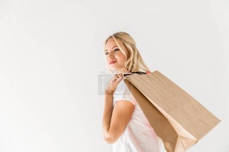 Photo pour Souriante jeune femme avec des sacs à provisions à la recherche de suite isolée sur blanc - image libre de droit