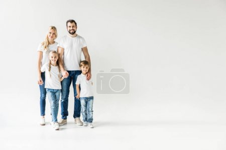 Photo for Happy young family in white t-shirts and denim pants looking at camera isolated on white - Royalty Free Image