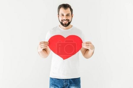Photo pour Bel homme barbu tenant symbole de coeur rouge et souriant à la caméra isolé sur blanc - image libre de droit