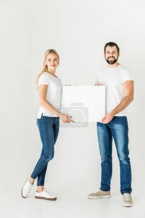 Photo for Happy young couple holding blank card isolated on white - Royalty Free Image