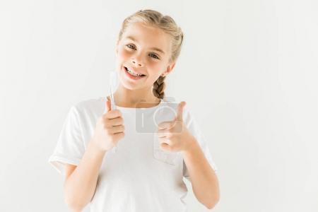 Photo pour Cute kid heureux holding brosse à dents et montrant le pouce en haut isolé sur blanc - image libre de droit