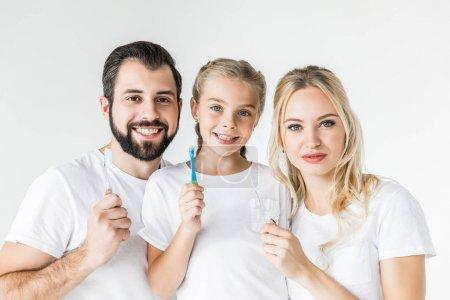 Photo pour Heureux jeune famille tenant des brosses à dents et souriant à la caméra isolé sur blanc - image libre de droit